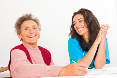 happy senior woman with caregiver laughing
