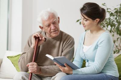 caregiver reading book to senior man