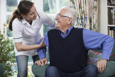 caregiver helping senior man to get up
