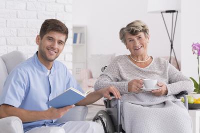 smiling elegant senior woman on wheelchair with caregiver